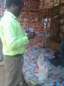 Police Criminal Investigations Department officer inspecting pirated CD-DVD at a market in Lilongwe Malawi - Credit COSOMA