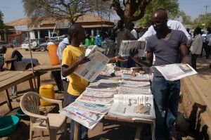 A man buys newspapers from a stand in the city of Juba.